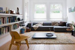 Niedriger Bauhaus Stuhl aus Holz vor dunklem Bodentisch auf flokatiartigem Teppich und graues Designer Sofa am Fenster