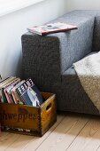 Vintage wooden crate of books next to partially visible modern couch with mottled grey fabric cover