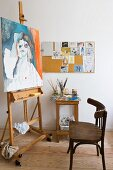 Simple wooden chair in front of painting on easel and painting utensils on side table against wall
