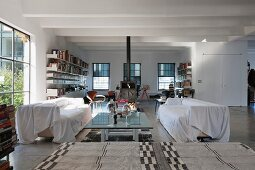 Covered sofas by a glass coffee table in a modern loft