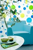 Blue armchair against wall with polka-dots in shades of green & blue
