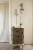 Vintage chest of drawers against pale wall in hallway