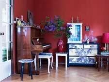 Glass display case on artistically painted chest of drawers, old piano and various vintage stools against red-painted wall