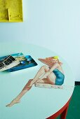 Round table top with photorealistic, fifties-style painting of woman in bathing suit sitting on diving board