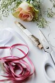 Ribbon, wire, scissors and a rose