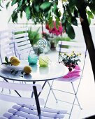 Hurricane candles and lemons on a patio table with folding chairs