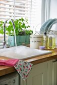 Water running into kitchen sink full of foam in country house kitchen
