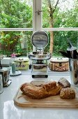 Bread on chopping board and various kitchen utensils on ceramic worksurface in front of kitchen window