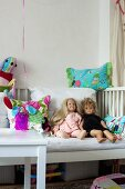 Dolls and colourful cushions on white child's bed