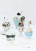 Unusual pincushions in painted eggcups with fabric 'hats'