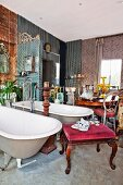 Twin freestanding bathtubs with standpipe tap fittings and various antique furnishings in crammed lounge-style bathroom