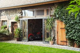 Country house with renovated shed and view of motorbike through open, sliding glass doors