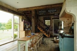 Open-plan, country-house-style living-dining room with rustic wooden floor and wooden staircase leading to mezzanine; open terrace window leading to garden