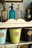 Antique soda siphons of different colours and glazed pots with royal seal on nostalgic, wall-mounted shelves with curved front panel