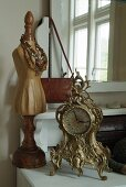 Ornate, Rococo-style table clock and necklaces draped on miniature tailors' dummy arranged on white dressing table