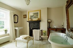 Bathroom with open fireplace and white tiled floor, large mirror above full bathtub, towels on ottomans and washstand in background