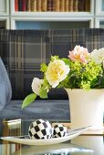 Chequered spheres on spindle-shaped dish and bouquet of roses in white ceramic vase