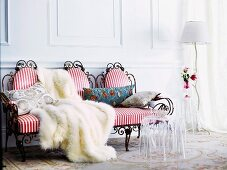 Romantic seating area with draped fur blanket on red and white striped upholstery of delicate, antique-style wire bench