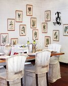 Covered chairs at set dining table in corner of room with framed pictures of ferns on whitewashed brick walls