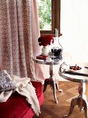 Elegant, chrome bistro table on parquet floor in front of window with floor-length curtains in boudoir