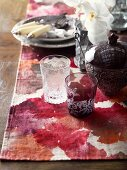 Vintage glasses and sugar bowl next to place setting on table runner with red, batik-effect pattern of leaves