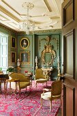 Baroque conference room with upholstered furniture, gilt-framed oil portraits and red rug