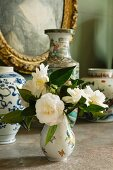 Posy of white roses in china vase in front of collection of vases and gilt-framed picture