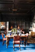 Festively set dining table in wood-panelled great hall with blue rug