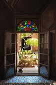 Inviting view of sunny courtyard planted with small trees and bushes from dark Oriental interior through open French doors with colourful stained glass in fanlight