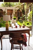 View from a wooden writing desk of a courtyard with an urn and sculptures