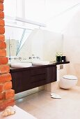 Brown washstand and base cabinet with two white, counter-top basins next to brick wall in designer bathroom