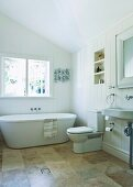Bright, spacious bathroom under the sloping roof with modern bathtub, stone tiles and large window