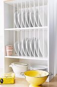 Stacked plates in a plate rack made from wooden dowels in kitchen shelves and yellow metal colander