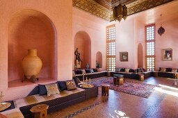 A salon marocain with velvet covered seating around walls and a Fez-work carved and painted ceiling