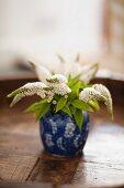 White profusion (Buddleia davidii) in a small blue vase