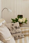 Cotton cushion cover made from linen grain sacks with german text on a beige and white gingham sofa