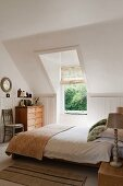 White double bedroom with sloping walls and Laura Ashley lamps
