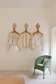 Antique Hungarian linen smocks and shirts hung decoratively on a white wall above a green Lloyd Loom chair