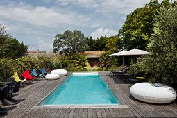 Colorful butterfly chairs and patio furniture on a large wooden terrace with a pool