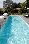 Man swimming in narrow pool on sunny wooden terrace with various seating