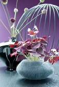 Gray felt vase with red clover in front of a ceramic vase with allium