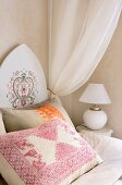 Embroidered cushion on bed with Oriental-style painted headboard and white, gathered canopy; spherical, white table lamp with simple lampshade on bedside cabinet
