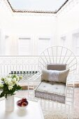 White, wooden, lattice chair with seat cushion in elegant loggia with view into small, bright, Oriental courtyard; closed courtyard doors around walls, eaves of tiled roof and open view of sky