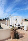 Blue sky above Oriental roof terrace with planters and modern, canopied daybed on terracotta floor