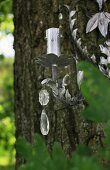 Cast metal, floral candlestick decorated with crystal pendants hanging on tree trunk in garden