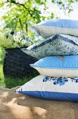 Stack of blue and white patterned cushions on terrace floor in summer garden