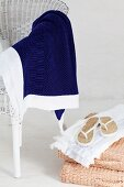 Blue blanket on white wicker chair next to white flip-flops on basketwork chair cushions
