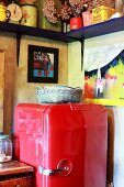 Red, retro fridge under small paintings and colourful pots on simple wooden shelf in corner of kitchen