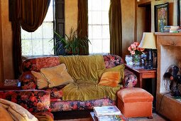 Floral sofa set with plain velvet blankets in cluttered vintage living room with open fireplace