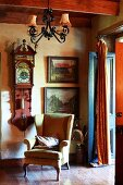 Wing-back chair and wrought iron chandelier in front of antique wall clock and old landscape paintings